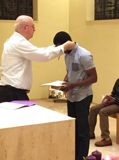 Fr. Dennis Gallagher, provincial, places a cross on newly accepted postulant, Matthew Mary Onyemaechi Okerete